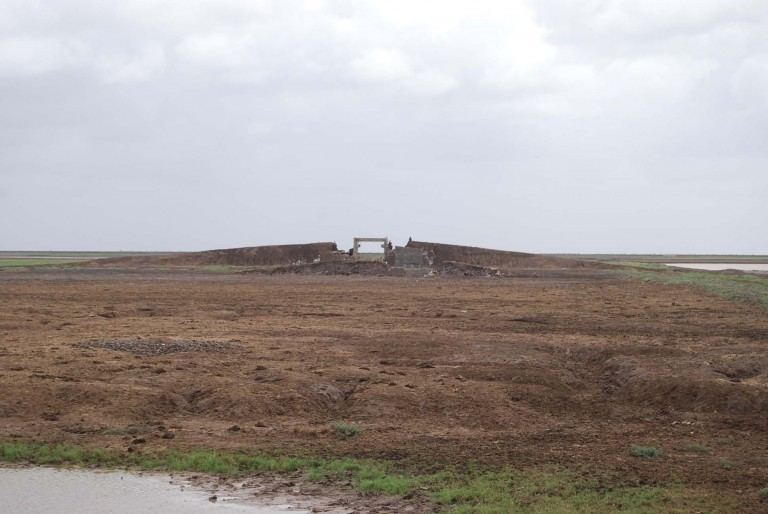 A bridge washed off by a storm along a road formed in the tidal flats.