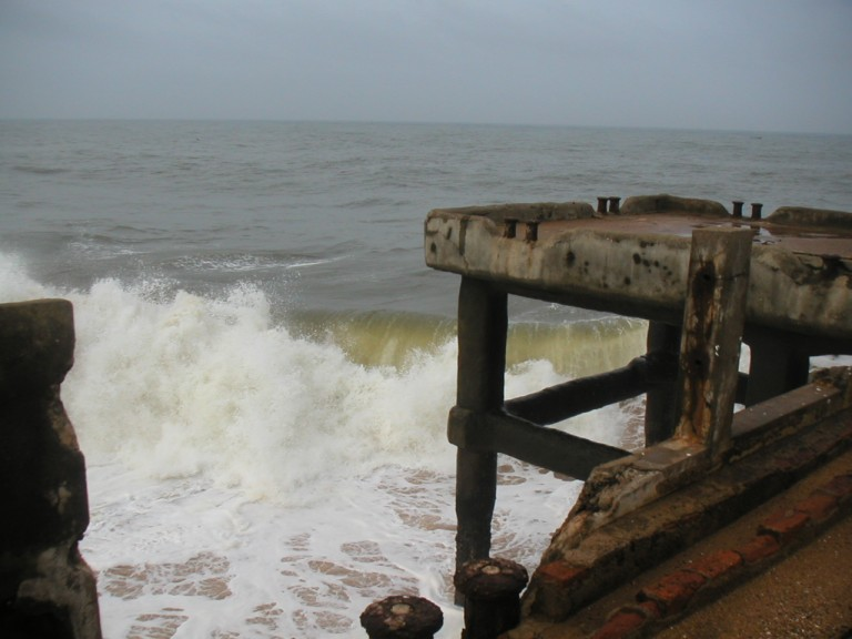 Wave lashing on concrete colums of dilapidated pier